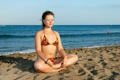 Muchacha agradable meditating en la playa Foto de archivo libre de regalías