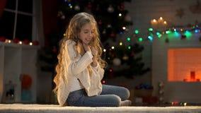 Muchacha agradable que abraza el sobre, soñando sobre regalos de Navidad, creencia en milagro imagen de archivo