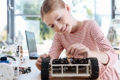 Muchacha agradable que acaba para arriba la construcción del vehículo robótico Foto de archivo libre de regalías