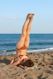 Muchacha agradable que hace ejercicios en la playa Imagen de archivo