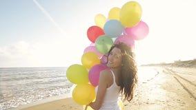 Muchacha agradable que juega con los globos en la playa