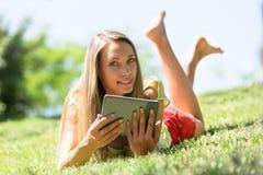Muchacha agradable que miente en la hierba que goza leyendo el ereader Imagenes de archivo