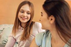 Muchacha agradable que mira a su más vieja hermana con sonrisa Fotografía de archivo