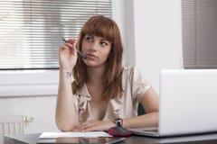 Muchacha agradable que piensa y que trabaja en el ordenador portátil Fotografía de archivo