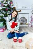 Muchacha agradable que se sienta cerca del árbol de navidad en un cuarto blanco Fotos de archivo