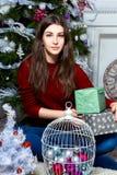 Muchacha agradable que se sienta cerca del árbol de navidad en un cuarto blanco Imágenes de archivo libres de regalías