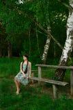 Muchacha agradable que se sienta en el bosque en el banco de madera Fotografía de archivo libre de regalías