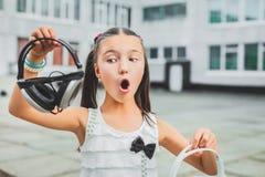 Muchacha agradable que sostiene el auricular Imágenes de archivo libres de regalías