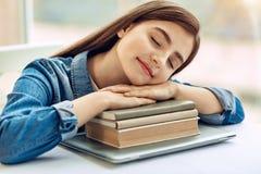 Muchacha agradable que toma siesta en la pila de libros Fotos de archivo libres de regalías