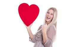 Muchacha aislada feliz joven con un corazón rojo para la tarjeta del día de San Valentín. Imagen de archivo