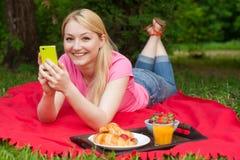 Muchacha al aire libre en el parque en comida campestre usando su teléfono celular Imágenes de archivo libres de regalías