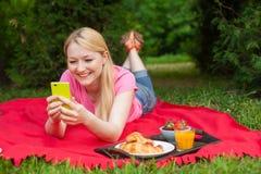 Muchacha al aire libre en el parque en comida campestre usando su teléfono celular Imagenes de archivo