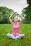 Muchacha al aire libre en el parque que hace yoga fotografía de archivo