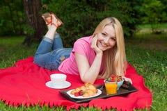 Muchacha al aire libre en el parque que tiene comida campestre en la hierba fotos de archivo libres de regalías