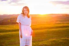 Muchacha al aire libre que disfruta de la naturaleza Mujer en la alineada blanca en campo Foto de archivo
