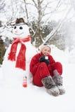 Muchacha al lado del muñeco de nieve con la bebida caliente Foto de archivo