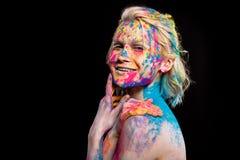 muchacha alegre atractiva que presenta en pintura colorida del holi foto de archivo