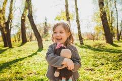 Muchacha alegre con el juguete en parque Fotografía de archivo libre de regalías