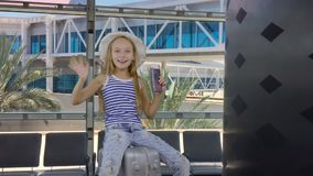 Muchacha alegre con el montar a caballo en la maleta mientras que espera en salón de la salida en aeropuerto almacen de video