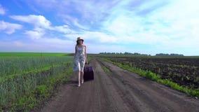 Muchacha alegre con la maleta que camina en el camino almacen de metraje de vídeo