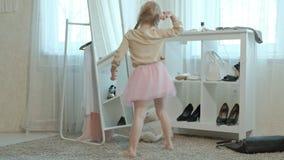 Muchacha alegre con las coletas que intentan en la ropa de la madre adulta, vestidos, tacones altos, bailando delante de un espej almacen de metraje de vídeo