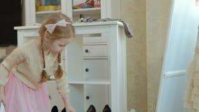 Muchacha alegre con las coletas que intentan en la ropa de la madre adulta, vestidos, tacones altos, bailando delante de un espej metrajes