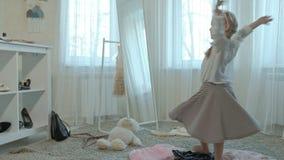 Muchacha alegre con las coletas que intentan en la ropa de la madre adulta, vestidos, tacones altos, bailando delante de un espej almacen de video
