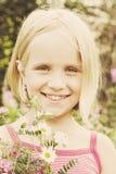 Muchacha alegre con las flores salvajes del verano Imágenes de archivo libres de regalías