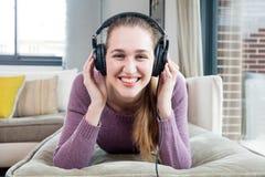 Muchacha alegre con los auriculares que se acuestan, disfrutando de escuchar la música Imagen de archivo libre de regalías