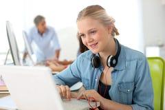 Muchacha alegre con los auriculares usando el ordenador portátil Fotografía de archivo