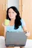 Muchacha alegre con una computadora portátil y una taza de café Fotografía de archivo libre de regalías