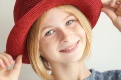 Muchacha alegre del adolescente con el sombrero rojo, aislado en blanco Fotos de archivo libres de regalías