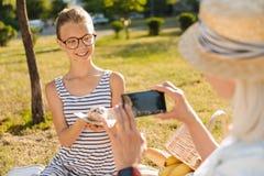 Muchacha alegre del adolescente que presenta en una comida campestre con los cruasanes Fotografía de archivo