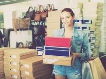 Muchacha alegre del adolescente que sostiene las cajas en boutique de los zapatos Fotografía de archivo