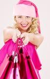 Muchacha alegre del ayudante de santa con los bolsos de compras Fotos de archivo libres de regalías