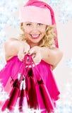 Muchacha alegre del ayudante de santa con los bolsos de compras Imagen de archivo