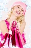 Muchacha alegre del ayudante de santa con los bolsos de compras imagen de archivo libre de regalías