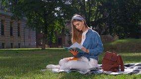 Muchacha alegre del estudiante que estudia sus notas Mujer joven que se sienta en la hierba en el parque, sosteniendo un cuaderno almacen de metraje de vídeo