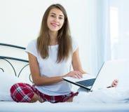 Muchacha alegre del estudiante studing con el ordenador portátil en cama Imagenes de archivo