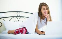 Muchacha alegre del estudiante studing con el ordenador portátil en cama Imagen de archivo libre de regalías