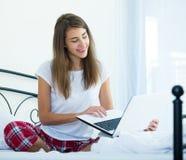Muchacha alegre del estudiante studing con el ordenador portátil en cama Imagen de archivo