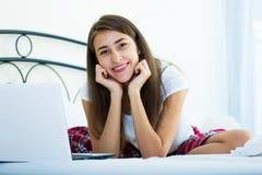 Muchacha alegre del estudiante studing con el ordenador portátil en cama Foto de archivo