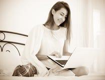 Muchacha alegre del estudiante studing con el ordenador portátil en cama Foto de archivo libre de regalías