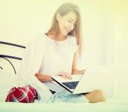 Muchacha alegre del estudiante studing con el ordenador portátil en cama Fotografía de archivo libre de regalías