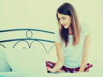Muchacha alegre del estudiante studing con el ordenador portátil en cama Fotos de archivo