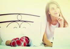 Muchacha alegre del estudiante studing con el ordenador portátil en cama Imágenes de archivo libres de regalías