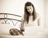 Muchacha alegre del estudiante studing con el ordenador portátil en cama Fotos de archivo libres de regalías