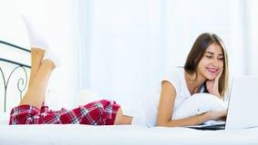 Muchacha alegre del estudiante studing con el ordenador portátil en cama Fotografía de archivo