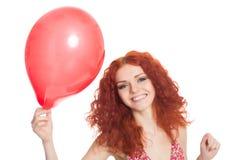 Muchacha alegre del pelirrojo que sostiene el globo rojo imagen de archivo