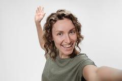 Muchacha alegre del pelo rizado que tiene v?deo-llamada con el selfie del tiroteo del amante en c?mara delantera foto de archivo libre de regalías